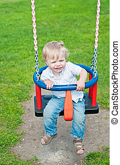 Cute baby boy playing on swing in park