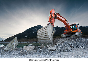 heavy organge excavator with shovel standing on hill with...