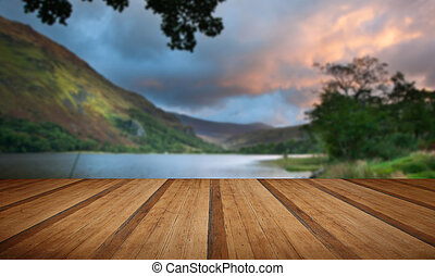Beautiful sunrise over lake and mountains with wooden planks...