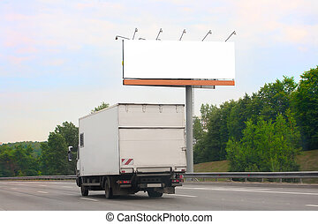 truck goes on highway by billboard - white truck goes on...