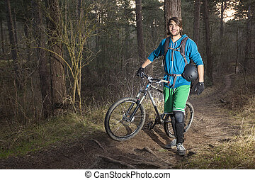 Young man with his ATB in the forest