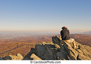 Man reflecting life while sitting on Humpback Rock in the...