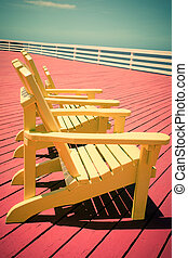 Adirondack Chairs - Vintage toned image of three yellow...