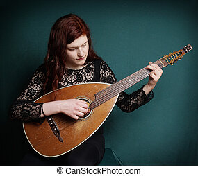 woman playing lute - young woman playing vintage lute...
