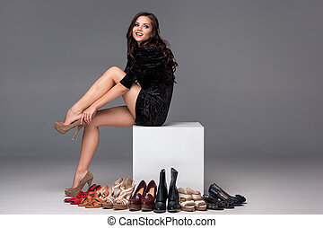 picture of sitting woman trying on high heeled shoes -...
