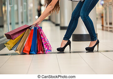 Woman legs with shopping bags against the backdrop of a...