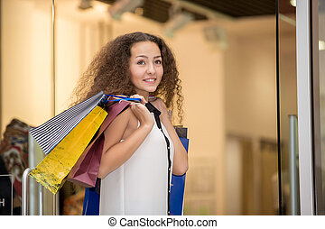 beautiful young woman with a shopping bags in the mall -...