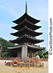 Deers flocking in front of majestic pagoda