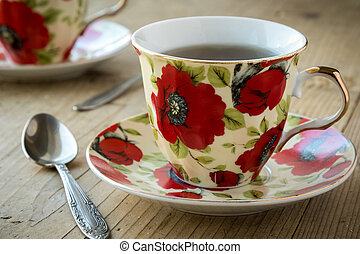 tea in vintage teacup with flower design on wooden table