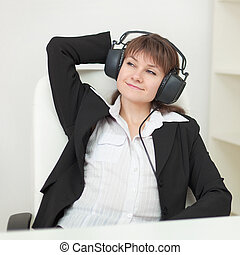The young girl with the big professional ear-phones on a head sits in an armchair