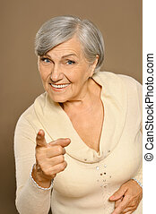 Senior woman pointing - Portrait of senior woman pointing at...