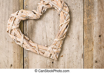 Braided heart in front of a rustic wooden background