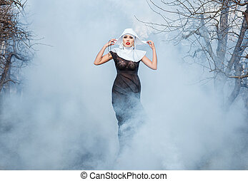 Nun in the smoke. - Glamour portrait of a girl nuns among...