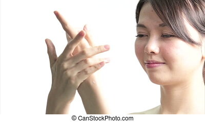 Chinese Woman Applying Cream to Hands, Medium Close Up in...