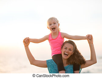 Happy baby girl sitting on shoulders of mother on beach in...