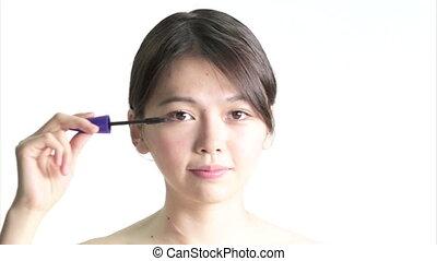 Chinese Woman Applying Mascara , Medium Close Up in studio...