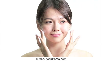 Chinese Woman Applying Cream to Face with Hands, Medium...