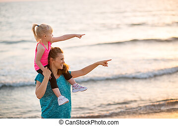 Happy baby girl sitting on shoulders of mother on beach in the e