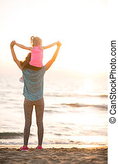 Baby girl sitting on shoulders of mother and rejoicing while...