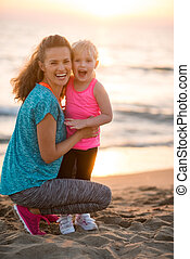 Portrait of healthy mother and baby girl on beach in the...