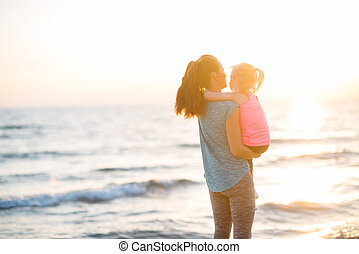 Healthy mother and baby girl looking into distance on beach in t