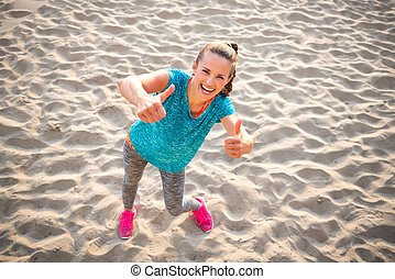 Happy fitness young woman on beach showing thumbs up