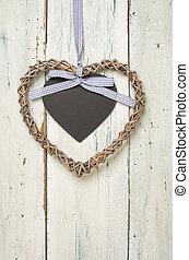 Geflochtesnes Herz mit Tafel vor weißen Holzbrettern -...