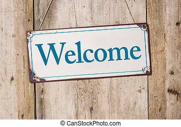 Old metal sign in front of a rustic wooden wall - Welcome