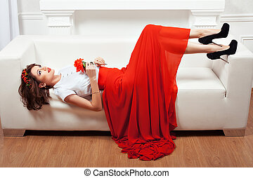 Girl in a white interior - Girl lying on the sofa, her red...