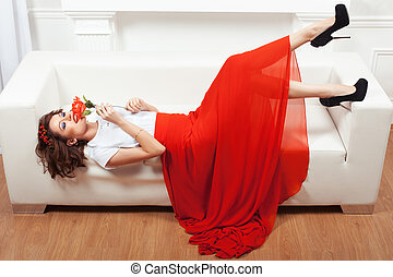 Girl with Rose on a sofa - Girl in red dress lying on a...