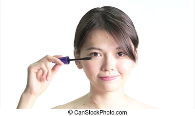 Chinese Woman Applying Mascara , Medium Close Up in studio...