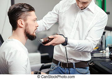 Man shaves his beard with a hair clipper - Perfectly styled...