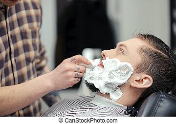 Client shaving at barber shop - Shaving the beard. Barber...