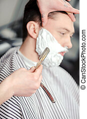 Client shaving at barber shop - Skillful barber. Young man...
