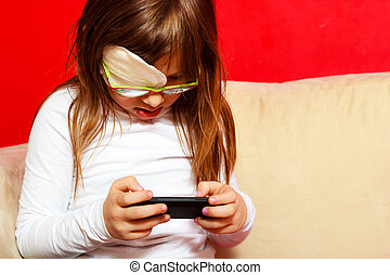 girl child in glasses playing games on smartphone at home -...
