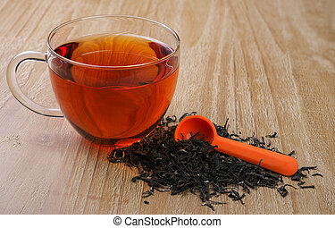 loose leaf tea - cup of tea and pile of loose leaf tea on...