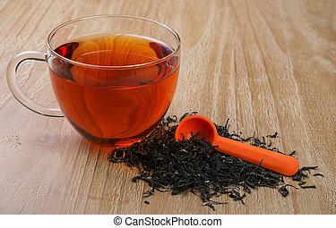 loose leaf tea - cup of tea and pile of loose leaf tea on...