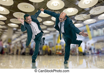 Pressed businessmen at the airport - Humorous shot of a pair...