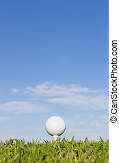 Golf ball on a tee with sky background - Golf ball on a tee...