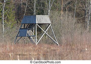 Wooden watchtower for birding in wetland during spring