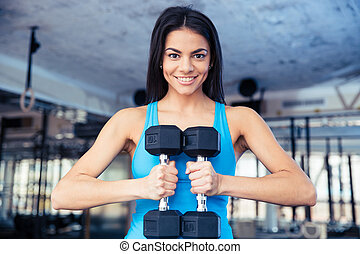 Happy fit woman holding dumbbells at gym