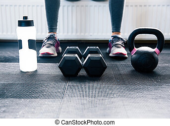 Closeup image of a woman sitting at gym with dumbbells,...