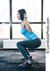 Young woman doing squats with barbell - Side view portrait...