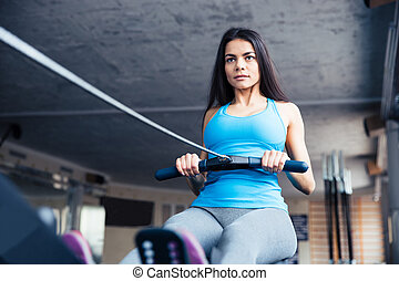Woman working out on training simulator - Attractive young...