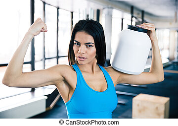 Fit woman showing her muscles and holding sports nutrition...