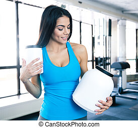 Happy young woman holding plastic container at gym - Happy...