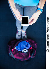 Closeup image of a woman holding smartphone