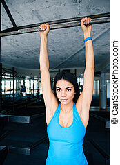 Attractive young woman pulls on crossbar at gym