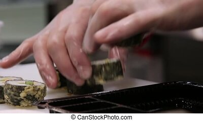 chef hands in gloves packing sushi rolls into container for...