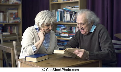 Retirement Pastime - Close up of senior couple reading a...